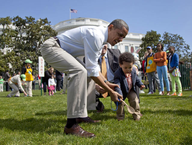 <p>President Barack Obama helps a little boy roll his egg to the finish line during the annual White House Easter Egg Roll, Monday, April 9, 2012, on the South Lawn of the White House in Washington. In the background, at left are Malia Obama and Sasha Obama. (Photo: Carolyn Kaster/AP) </p>