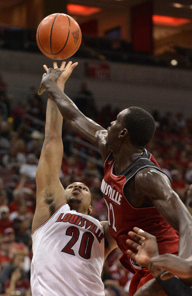 Louisville's Mangok Mathiang, right, fouls Wayne Blackshear as he attempts a shot during their NCAA college basketball scrimmage Saturday, Oct. 5, 2013, in Louisville, Ky. (AP Photo/Timothy D. Easley)