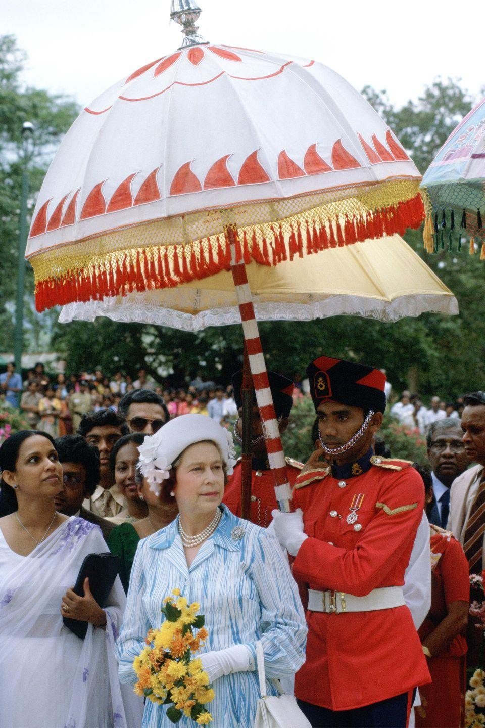 <p>In a blue and white striped dress with a matching hat, the queen carried a bouquet of yellow flowers when she visited the Peradeniya Gardens in Sri Lanka.</p>