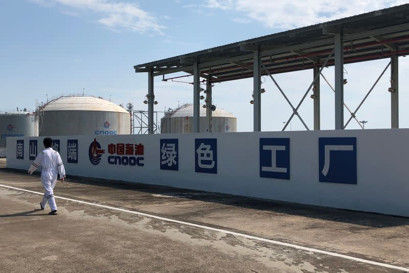 FILE PHOTO: Worker walks past the logo of China National Offshore Oil Corporation (CNOOC) at its Nanshan liquefied natural gas (LNG) terminal in Hainan