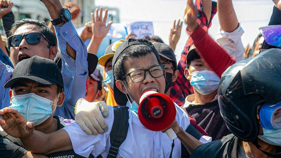 Protesters shout slogans through a megaphone at the junction