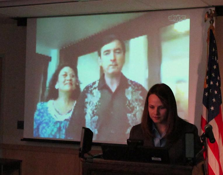 Anchorage Mayor Dan Sullivan, shown on screen with his wife Lynnette, prepares to take the oath of office via live video link from Honolulu as administered by a judge in Anchorage, Alaska, on Monday, July 2, 2012. Sullivan had a previously scheduled family vacation, and was sworn in Monday from a lawyer's office in Honolulu. At right is the mayor's spokeswoman, Lindsey Whitt. (AP Photo/Rachel D'Oro)