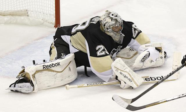 Pittsburgh Penguins goalie Marc-Andre Fleury fans out as he stops a shot by the Washington Capitals during the third period of an NHL hockey game, Tuesday, March 11, 2014, in Pittsburgh. The Penguins won 2-0.(AP Photo/Keith Srakocic)