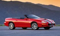 """<p>By the turn of the 21st century, the Camaro was both an old product and, seemingly, an irrelevant and archaic one. """"Although GM has done a good job of keeping the F-car chassis viable,"""" <a href=""""http://www.caranddriver.com/comparisons/1999-chevrolet-camaro-z28-vs-ford-mustang-gt-archived-comparison"""" rel=""""nofollow noopener"""" target=""""_blank"""" data-ylk=""""slk:wrote our own Tony Swan"""" class=""""link rapid-noclick-resp"""">wrote our own Tony Swan</a> in 1999, """"it's still a live rear axle setup, and it shows us, once again, that live axles have definite handling limits, particularly on bumpy roads. In this case we found that oversteer was just one injudicious stab of the throttle away, and one tester went so far as to call the Z28's handling 'spooky.' """" Still, it was quick, running from zero to 60 mph in 5.2 seconds and knocking off the quarter-mile in 13.8 seconds at 104 mph. Chevy celebrated the Camaro's 35th anniversary with a special graphics package on the Z28 SS coupe and convertible—and then killed the car. Seemingly forever.</p>"""