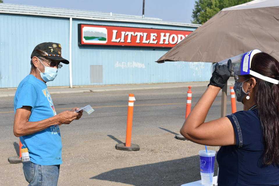 Linda Morrison, right, speaks with a man about participating in the U.S. Census on the Crow Indian Reservation in Lodge Grass, Mont. on Wednesday, Aug. 26, 2020. With millions of federal dollars for impoverished communities on the line, tribes across the U.S. are racing to avoid being undercounted, again in the census. (AP Photo/Matthew Brown)