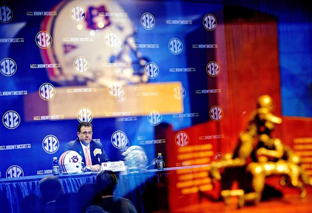 Auburn head coach Gus Malzahn is reflected in a glass case showcasing his team's helmet, top left, and the Southeastern Conference championship trophy at right, as he pauses while speaking at a press conference ahead of Saturday's SEC championship college football game against Missouri, Friday, Dec. 6, 2013, in Atlanta. (AP Photo/David Goldman)
