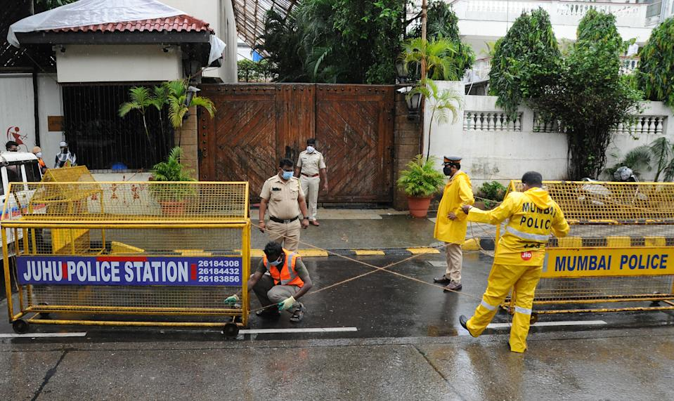 Policemen wearing facemasks seal the space outside Bollywood actor Amitabh Bachchan's bungalow with barriers. Bollywood actor Amitabh Bachchan tested positive for coronavirus and has been admitted to a hospital where he is being kept in quarantine. The actor requested those who had come in close proximity in the past ten days to get themselves tested for the virus. (Photo by Ashish Vaishnav/SOPA Images/LightRocket via Getty Images)