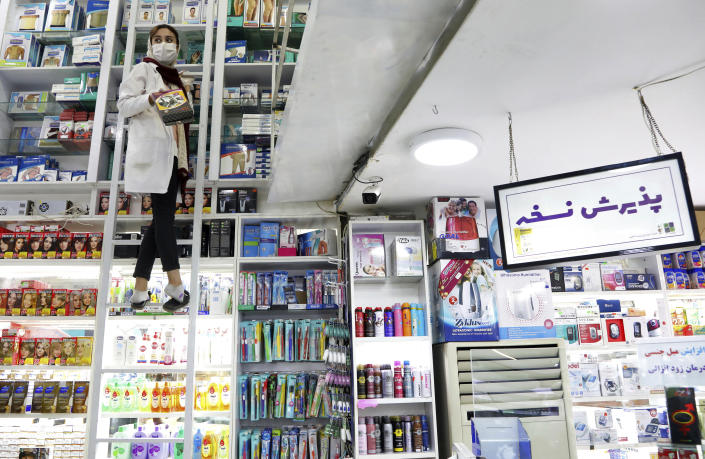A pharmacist works in a drugstore in downtown Tehran, Iran, Tuesday, Feb. 25, 2020. The head of Iran's counter-coronavirus task force has tested positive for the virus himself, authorities announced Tuesday, showing the challenges facing the Islamic Republic amid concerns the outbreak may be far wider than officially acknowledged. The announcement comes as countries across the Mideast say they've had confirmed cases of the virus that link back to Iran, which for days denied having the virus. (AP Photo/Ebrahim Noroozi)