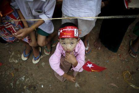 A child holds a National League for Democracy (NLD) party flag as he waits for Myanmar pro-democracy leader Aung San Suu Kyi during her campaign in her constituency of Kawhmu township outside Yangon September 21, 2015. REUTERS/Soe Zeya Tun
