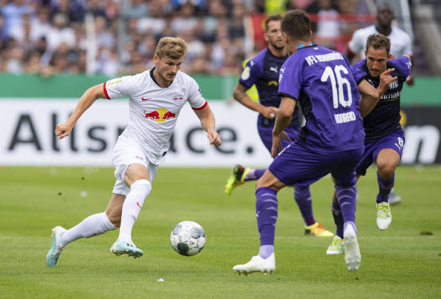 Leipzig's Timo Werner, left, challenges for the ball with Osnabrueck's Thomas Konrad, right, during the German soccer cup, DFB Pokal, first Round match between VfL Osnabrueck - RB Leipzig in Osnabrueck, Sunday, Aug. 11, 2019. (Guido Kirchner/dpa via AP)