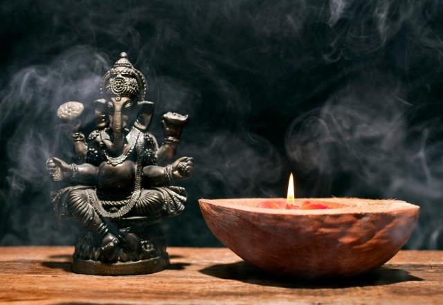 Hindu deity statue and candle.