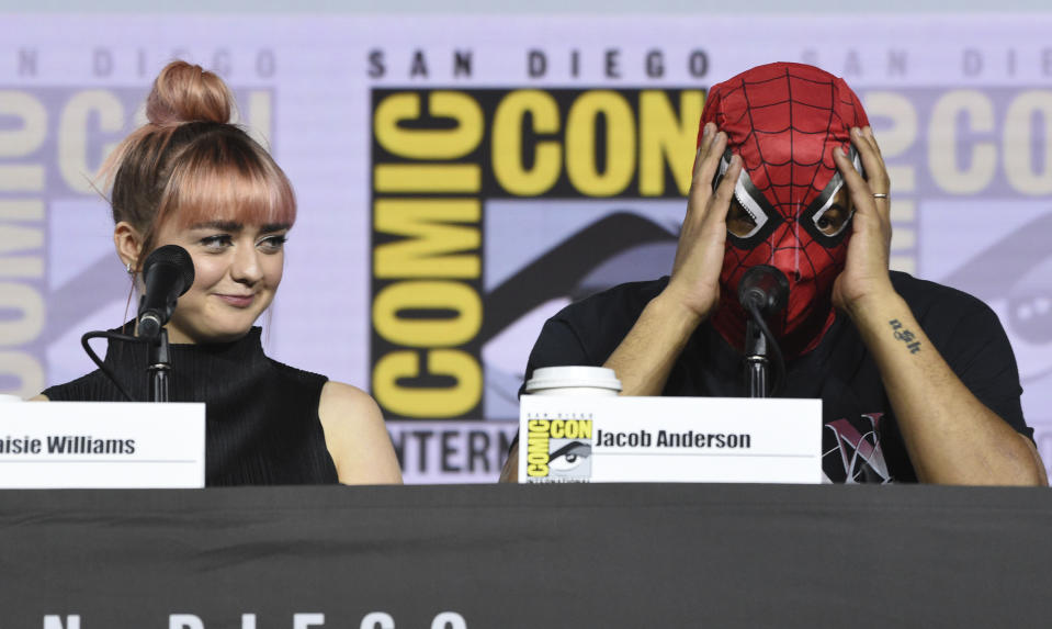 """Maisie Williams, left, looks at Jacob Anderson as he puts on a Spider-Man mask during the """"Game of Thrones"""" panel on day two of Comic-Con International on Friday, July 19, 2019, in San Diego. (Photo by Chris Pizzello/Invision/AP)"""