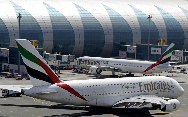 Emirates passenger planes are parked at their gates at Dubai airport in United Arab Emirates, Thursday, May 8, 2014. The parent company of the Middle East's biggest airline, Emirates, posted an annual profit Thursday of $1.1 billion as it enjoyed a dip in fuel costs and boosted capacity with the addition of two dozen new planes. (AP Photo/Kamran Jebreili)