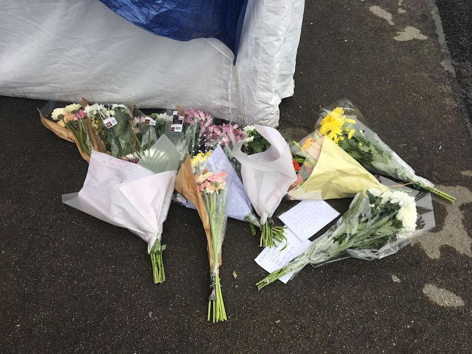 Tributes were left outside the entrance to the block of flats in Enfield (Picture: PA)