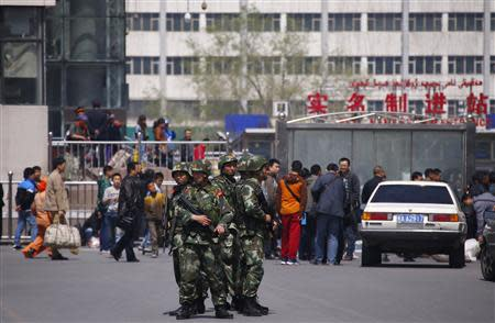 Paramilitary policemen stand guard near the exit of the South Railway Station in Urumqi