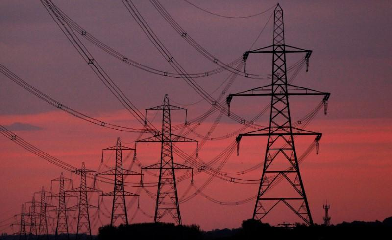 FILE PHOTO: The sun rises behind electricity pylons near Chester