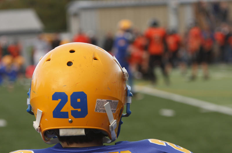 A football player watching his teammates on the field.