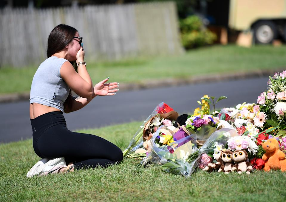 A friend of the victims named Korri Loader reacts at a makeshift shrine near the scene of the car fire. Source: AAP