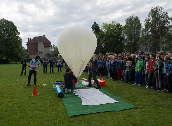 Students gather to watch researchers prepare the Small Photon-Entangling Quantum System for a test launch aboard a weather balloon at a field near Heinrich-Suso-Gymnasium Konstanz in Germany.