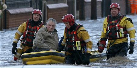 Emergency rescue service workers evacuate a resident in an inflatable boat in flood water in a residential street in Rhyl, north Wales December 5, 2013. REUTERS/Phil Noble