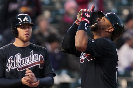 Atlanta Braves' Juan Francisco, right, looks upward after hitting a two-run home run scoring teammate Freddie Freeman, left, during the fourth inning of the second baseball game of a doubleheader against the Colorado Rockies Tuesday, April 23, 2013 in Denver. (AP Photo/Barry Gutierrez)