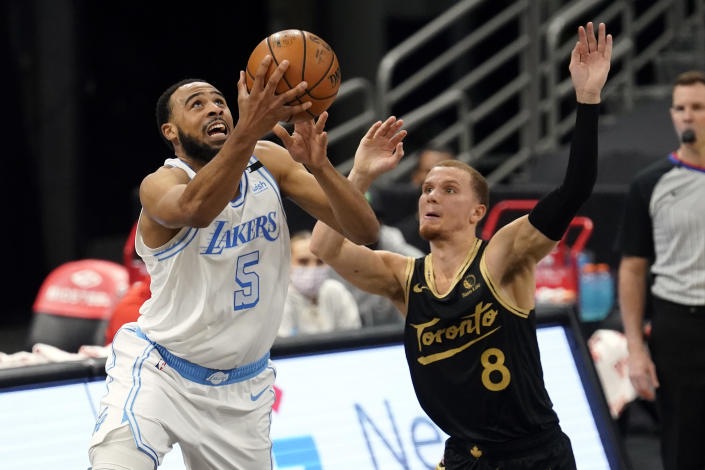 Los Angeles Lakers guard Talen Horton-Tucker (5) goes for a layup in front of Toronto Raptors guard Malachi Flynn (8) during the second half of an NBA basketball game Tuesday, April 6, 2021, in Tampa, Fla. (AP Photo/Chris O'Meara)