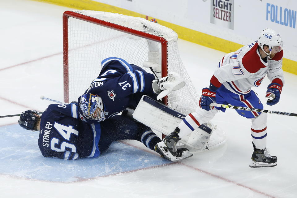 Winnipeg Jets' Logan Stanley (64) crashes into goaltender Connor Hellebuyck (37) as Montreal Canadiens' Brett Kulak (77) skates past during the third period of Game 1 of an NHL hockey Stanley Cup second-round playoff series Wednesday, June 2, 2021, in Winnipeg, Manitoba. (John Woods/The Canadian Press via AP)
