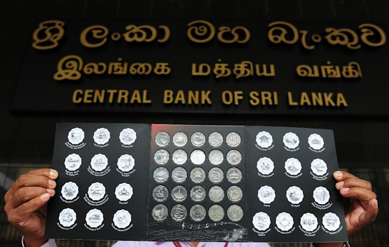 A Central Bank employee shows a series of new coins that were first given to Sri Lankan President Mahinda Rajapakse in Colombo on November 17, 2014 (AFP Photo/Lakruwan WANNIARACHCHI)