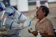 A taxi driver is tested by health workers in a carpark in Hong Kong