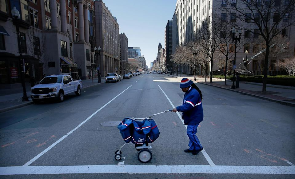 A USPS letter carrier crosses Boston Street with greatly reduced traffic during the coronavirus outbreak in March. (Lane Turner/The Boston Globe via Getty Images)