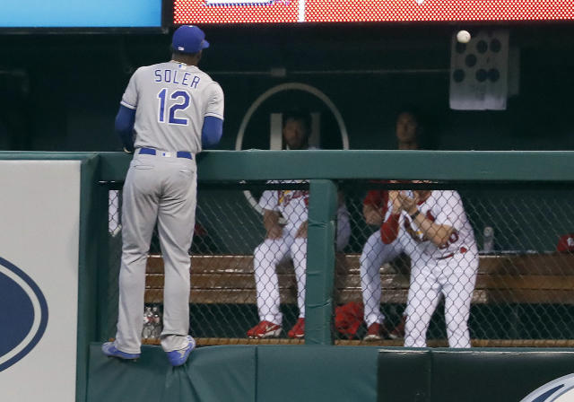 Kansas City Royals right fielder Jorge Soler climbs the outfield fence as he watches a three-run home run by St. Louis Cardinals' Tyler O'Neill during the third inning of a baseball game Monday, May 21, 2018, in St. Louis. (AP Photo/Jeff Roberson)