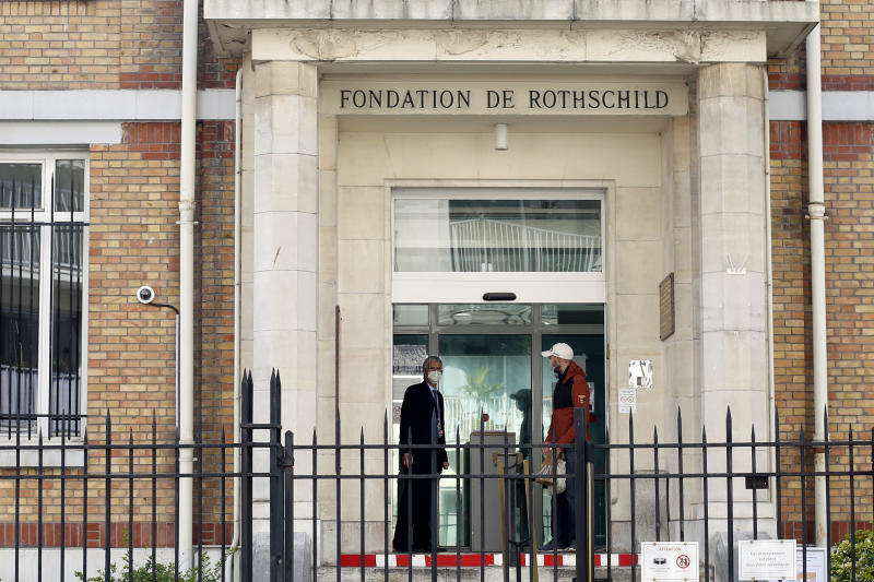 In this photo taken on Friday March 27, 2020 men wearing face masks chat at the entrance of the Fondation Rothschild nursing home, in Paris. Governments in Europe's hardest-hit countries have yet to systematically test the residents of nursing homes or those who receive in-home care. In Spain, Italy and France, which together account for a third of the world's confirmed coronavirus cases, no one knows for sure how many people have become sick and died of coronavirus, especially among the elderly. The new coronavirus causes mild or moderate symptoms for most people, but for some, especially older adults and people with existing health problems, it can cause more severe illness or death. (AP Photo/Thibault Camus)