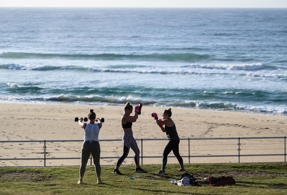 Three people exercise at Bondi Beach. This means exercise bootcamps will have to be limited to one-on-one sessions.