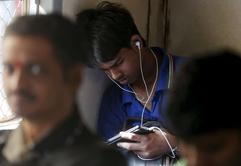FILE PHOTO: A man watches a video on his mobile phone as he commutes by a suburban train in Mumbai