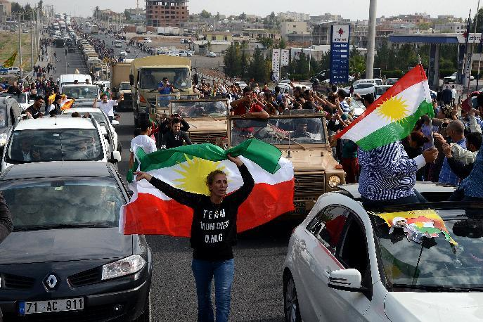 Kurds in Turkey cheer and wave flags as peshmerga convoys cross the Turkish-Iraqi border on October 29, 2014 (AFP Photo/Ilyas Akengin)