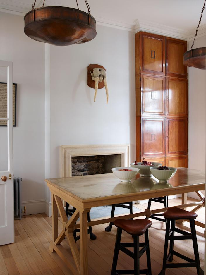 On the first floor, the dining room sits between the living room and kitchen. A pair of Apsley copper dish lights from Jamb hang above a Jamb Arts and Crafts–style oak table with a sheet brass top.