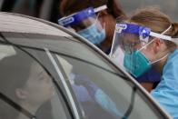 A medical worker administers a test at a drive-through COVID-19 testing centre in Sydney