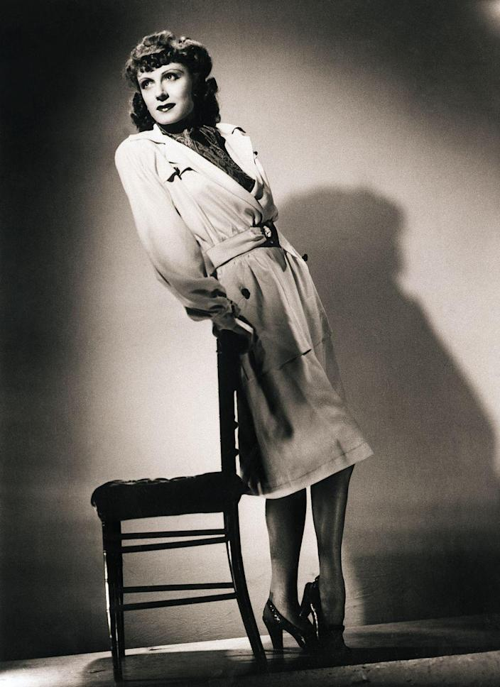 <p>Judith Evelyn wears an off-white gabardine suit, casually cut, with simple lines for both the skirt and belted jacket. Her shoes match the brown leather buttons on the suit pocket, and she wears a liberty scarf as an ascot. </p>