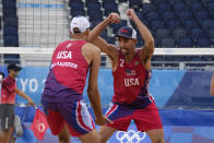 Nicholas Lucena, center, of the United States, celebrates with teammate Philip Dalhausser during a men's beach volleyball match at the 2020 Summer Olympics, Tuesday, July 27, 2021, in Tokyo, Japan. (AP Photo/Petros Giannakouris)