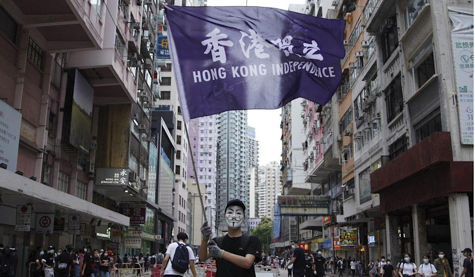 "A protester wearing a Guy Fawkes mask waves a ""Hong Kong Independence"" flag on Johnston Road in Wan Chai during a demonstration last year. Photo: Winson Wong"