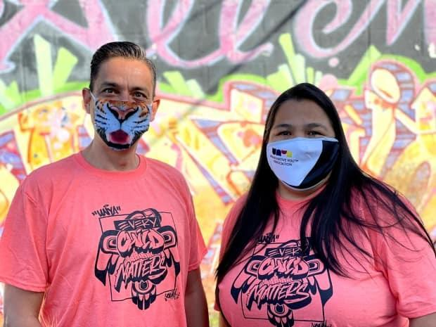 Robert Pacey and Cheryl Robinson model the orange shirts they worked together to created, to raise money for the Urban Native Youth Association in Vancouver, B.C. (Submitted by Robert Pacey - image credit)