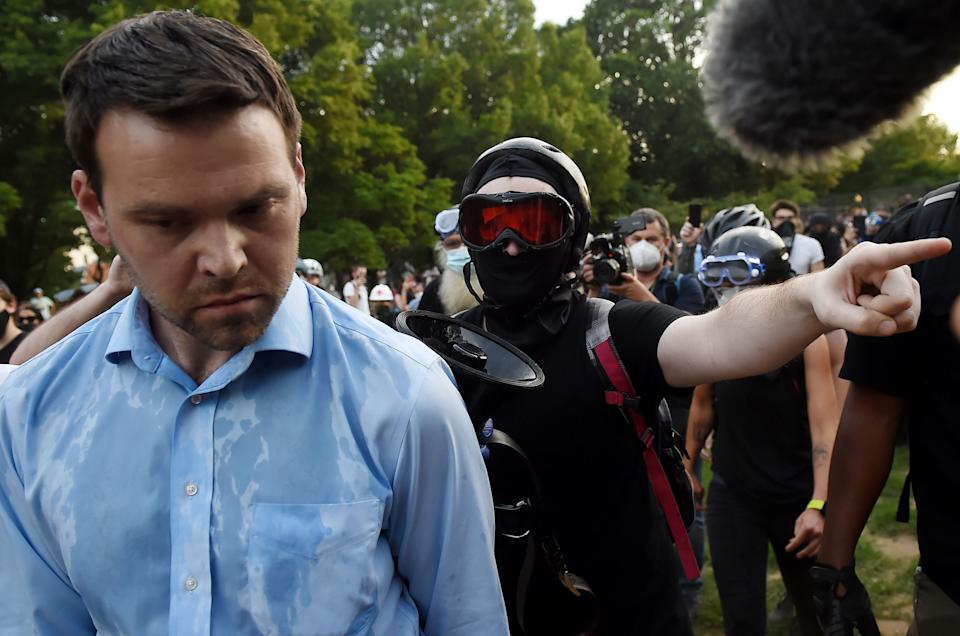 Far-right pro-Trump propagandist and One America News correspondent Jack Posobiec is escorted out of Lincoln Park by anti-racism protesters in Washington, D.C., on June 26. (Photo: OLIVIER DOULIERY/AFP via Getty Images)