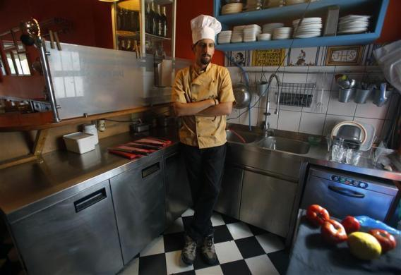Manolis Ouranos, a 30 year-old cook, poses in the Mavros Gatos (Black Cat) tavern in Psiri neighborhood in central Athens, May 23, 2012. Manolis studied at Athens Technology University (TEI) for four years where he received a degree in civil engineering. He hoped to find a permanent job in public sector infrastructure but has been working as a cook for four months instead. He now takes cooking lessons which he funds with his salary as a cook.