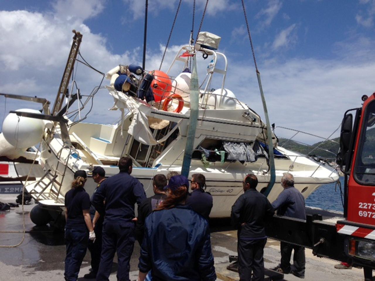 Coast guard officers prepare to tow a yacht that was used to carry immigrants that overturned, at the port of Vathy on the Greek island of Samos, Greece, on Monday, May 5, 2014. At least 22 people drowned including four children, in the incident in the eastern Aegean Sea, while 36 were rescued and others remain missing. (AP Photo/SamosTimes.gr)