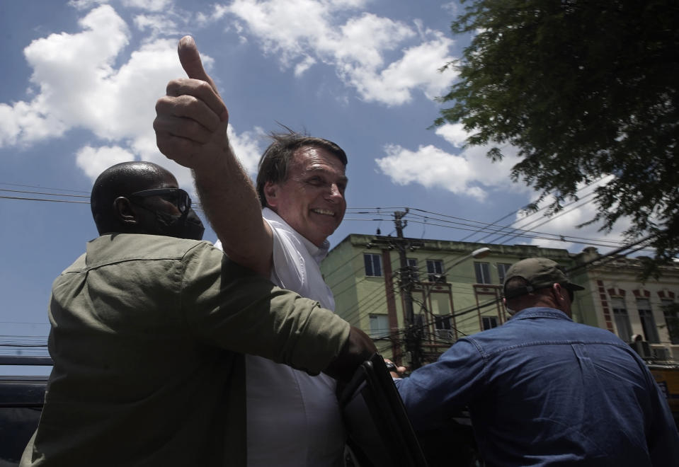 "Brazil's President Jair Bolsonaro greets supporters after voting during the run-off municipal elections in Rio de Janeiro, Brazil, Sunday, Nov. 29, 2020. Bolsonaro, who sometimes has embraced the label ""Trump of the Tropics,"" said Sunday he'll wait a little longer before recognizing the U.S. election victory of Joe Biden, while also echoing President Donald Trump's allegations of irregularities in the U.S. vote. (AP Photo/Silvia Izquierdo)"