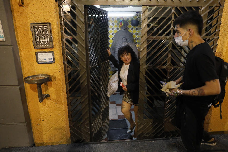 Sex worker Angeles walks out of the building where she and her partner, also a sex worker, live together in a small rented room with a shared hallway bathroom, as she heads back to work after running home to pick up forgotten high heels, in Mexico City, Tuesday, March 9, 2021. The 65-year-old who is living with HIV takes her health seriously and appreciates that since the coronavirus pandemic hit, hotels are requiring face masks and hand sanitizing, and are spraying disinfectant in the rooms between customers. (AP Photo/Rebecca Blackwell)