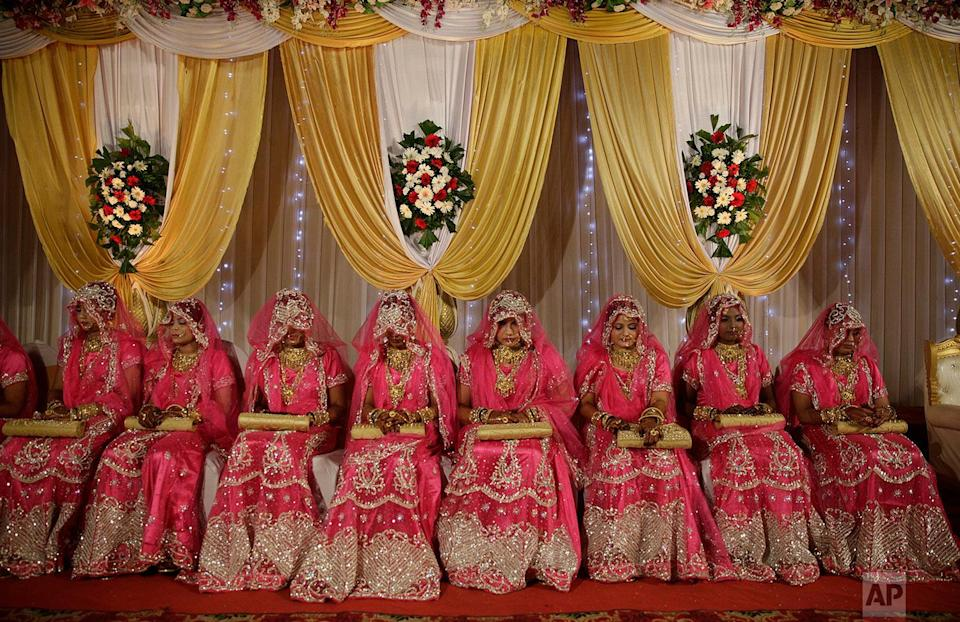<p>Brides sit for a mass marriage event in Mumbai, India. Mass weddings in India are organized by social organizations primarily to help the economically backward families who cannot afford the high ceremony costs as well as the customary dowry and expensive gifts that are still prevalent in many communities. (AP Photo/Rafiq Maqbool) </p>