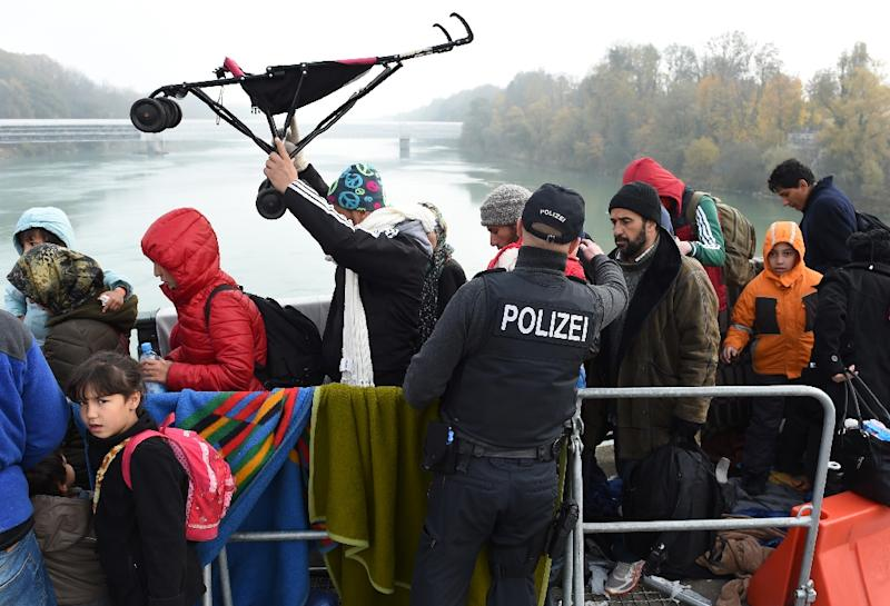 "Migrants cross the Austrian-German border at the ""Innbruecke"" bridge near the Austrian village of Braunau and the German village Simbach am Inn, southern Germany, on October 28, 2015 (AFP Photo/Christof Stache)"