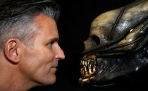 Stephen Lane, CEO of Prop Store, poses for a photograph with a special effects mechanical head from the film Alien at a preview of a movie and TV memorabilia auction in Rickmansworth