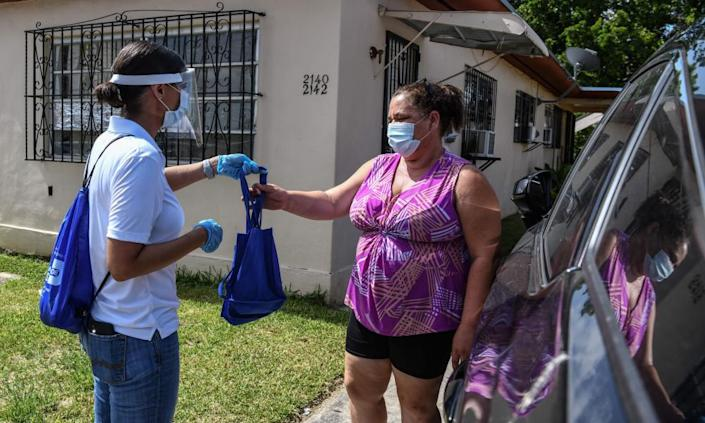 "<span class=""element-image__caption"">Catherimarty Burgos, a member of a local 'surge team', distributes bags with masks, sanitizers, and gloves in Miami.</span> <span class=""element-image__credit"">Photograph: Chandan Khanna/AFP/Getty Images</span>"